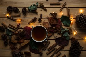 cinnamon sticks and lights on a table with a cup of tea